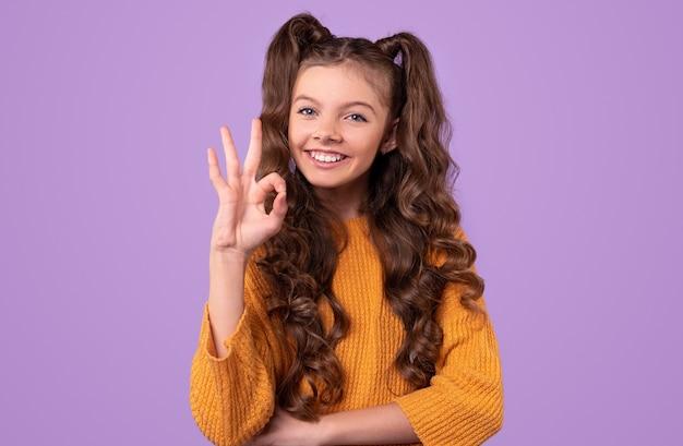 Erfreutes jugendlich mädchen mit langen gewellten zöpfen, die lässigen gestrickten pullover tragen, der okay zeichen mit den fingern schaut und zeigt