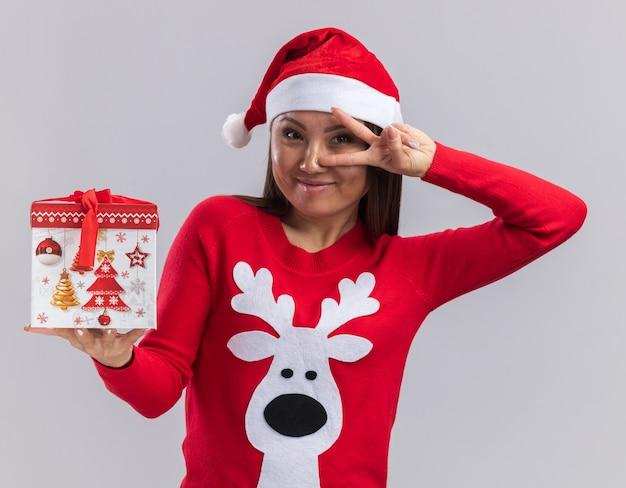 Erfreutes junges asiatisches mädchen, das weihnachtshut mit pullover hält, der geschenkbox hält, die friedensgeste lokalisiert auf weißem hintergrund zeigt
