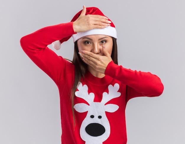 Erfreutes junges asiatisches mädchen, das weihnachtsmütze mit pullover bedeckt stirn und mund mit händen auf weißem hintergrund trägt