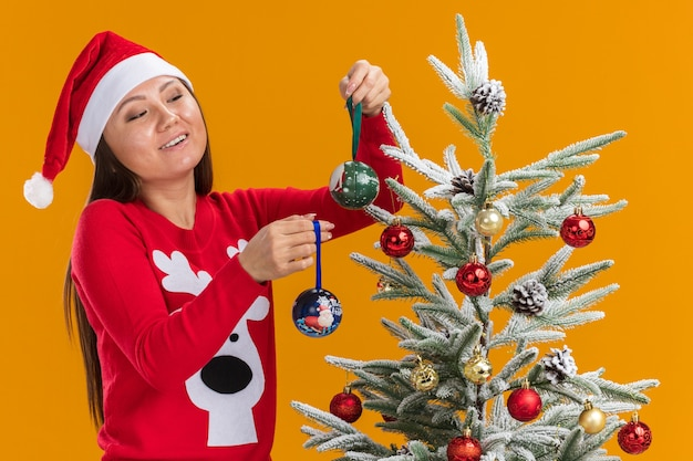 Erfreutes junges asiatisches mädchen, das weihnachtsmütze mit pullover trägt, verziert weihnachtsbaum lokalisiert auf orange hintergrund