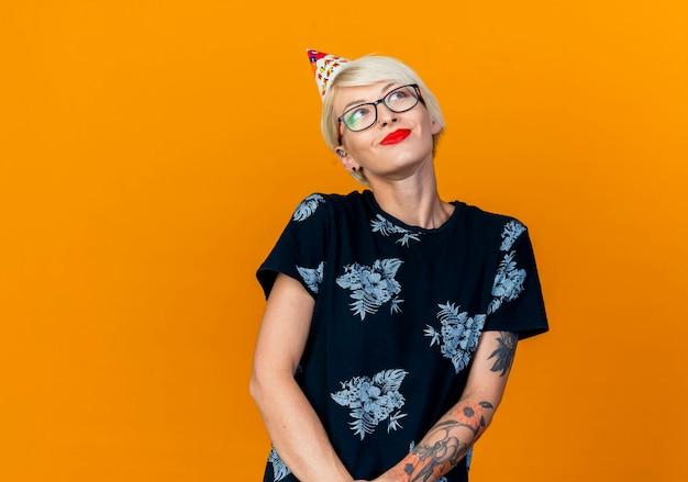 Erfreutes junges blondes partygirl, das brille und geburtstagskappe trägt, die seite betrachten, die hände zusammen auf orange hintergrund mit kopienraum hält