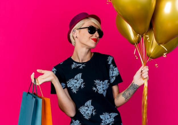 Erfreutes junges blondes partygirl, das partyhut und sonnenbrille hält, die luftballons und papiertüten lokalisiert auf purpurrotem hintergrund halten