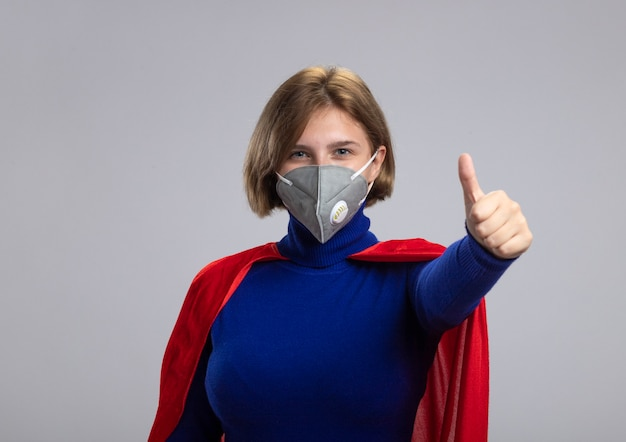 Erfreutes junges blondes superheldenmädchen im roten umhang, der schutzmaske betrachtet, die kamera zeigt, die oben auf weißem hintergrund mit kopienraum lokalisiert zeigt