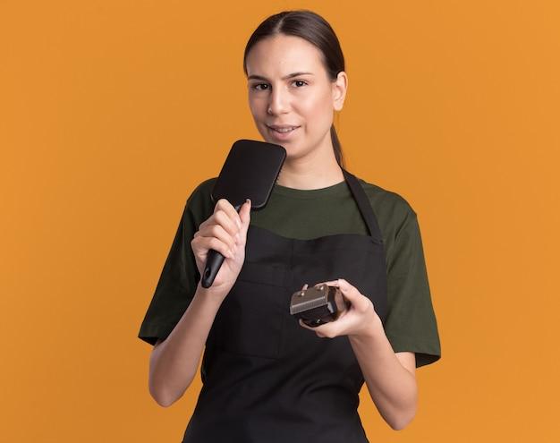 Erfreutes junges brünettes friseurmädchen in uniform hält haarschneidemaschinen und kamm, die vorgeben, auf orange zu singen