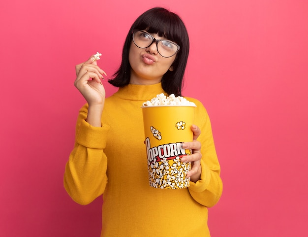 Erfreutes junges brünettes kaukasisches mädchen in optischer brille hält popcorn-eimer und sieht zur seite