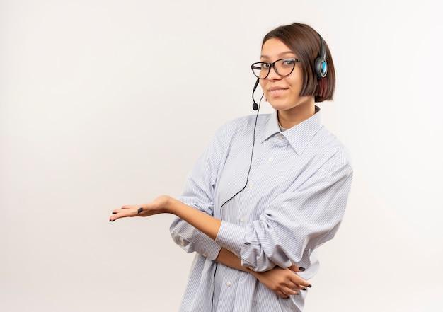 Erfreutes junges callcenter-mädchen, das brille und headset trägt und leere hand lokalisiert auf weißem hintergrund mit kopienraum zeigt