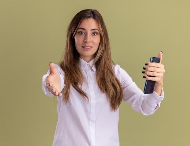 Erfreutes junges hübsches kaukasisches mädchen, das telefon hält und hand auf olivgrün ausstreckt