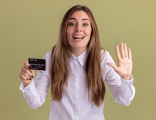Erfreutes junges hübsches kaukasisches mädchen hält kreditkarte und gestikuliert fünf auf olivgrün