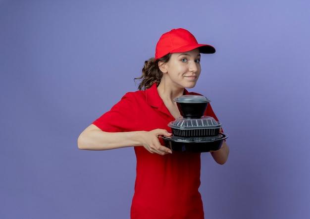 Erfreutes junges hübsches liefermädchen, das rote uniform und kappe hält, die lebensmittelbehälter lokalisiert auf lila hintergrund mit kopienraum hält