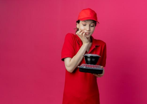 Erfreutes junges hübsches liefermädchen, das rote uniform und kappe hält und lebensmittelbehälter mit hand auf kinn lokalisiert auf purpurrotem hintergrund mit kopienraum hält