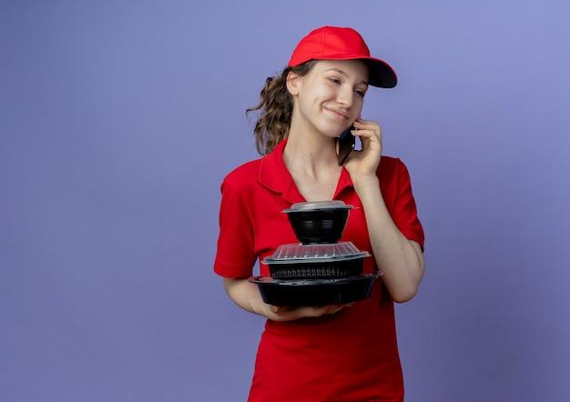 Erfreutes junges hübsches liefermädchen, das rote uniform und kappe trägt, die seite betrachtet, die lebensmittelbehälter hält und am telefon lokalisiert auf lila hintergrund mit kopienraum spricht