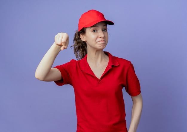 Erfreutes junges hübsches liefermädchen, das rote uniform und kappe trägt, tut so, als würde sie etwas lokalisiert auf lila hintergrund mit kopienraum halten