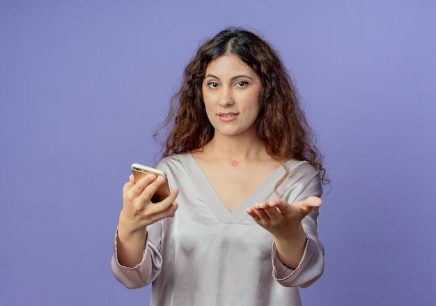 Erfreutes junges hübsches mädchen, das telefon hält und hand zur kamera hält, die auf blau lokalisiert wird