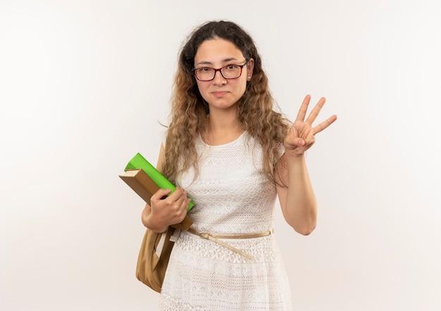 Erfreutes junges hübsches schulmädchen, das brille und rückentasche hält bücher hält, die drei mit hand lokalisiert auf weißer wand zeigen