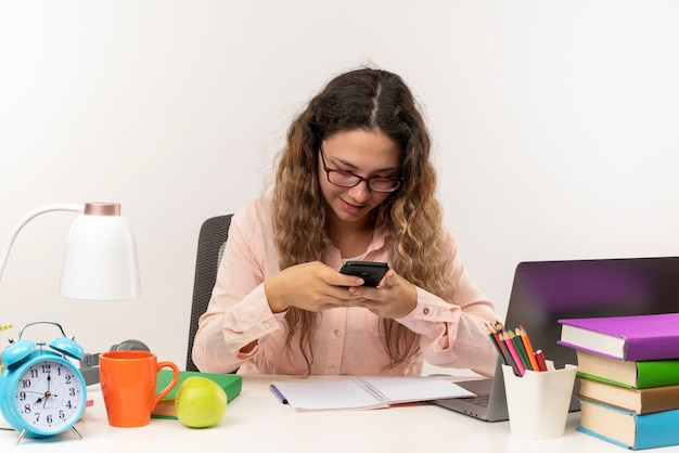 Erfreutes junges hübsches schulmädchen, das eine brille trägt, die mit schulwerkzeugen am schreibtisch sitzt und ihre hausaufgaben unter verwendung ihres auf weißer wand isolierten telefons macht