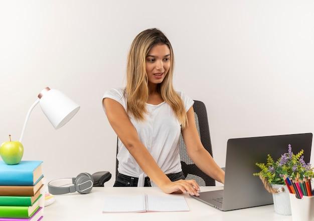 Erfreutes junges hübsches studentenmädchen, das hinter schreibtisch mit schulwerkzeugen steht und laptop verwendet, der auf weißer wand lokalisiert wird