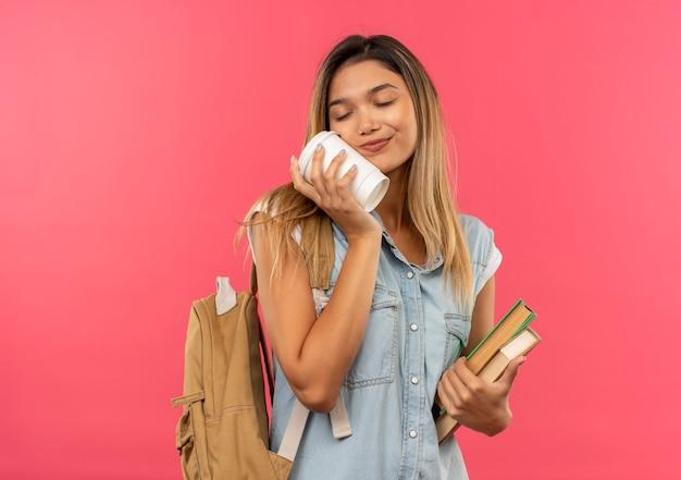 Erfreutes junges hübsches studentenmädchen, das rückentasche hält bücher hält und gesicht mit plastikkaffeetasse mit geschlossenen augen lokalisiert auf rosa wand mit geschlossenen augen berührt