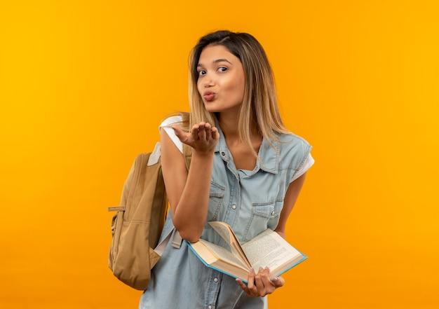 Erfreutes junges hübsches studentenmädchen, das rückentasche hält, offenes buch hält und schlagkuss an der vorderseite lokalisiert auf orange wand sendet