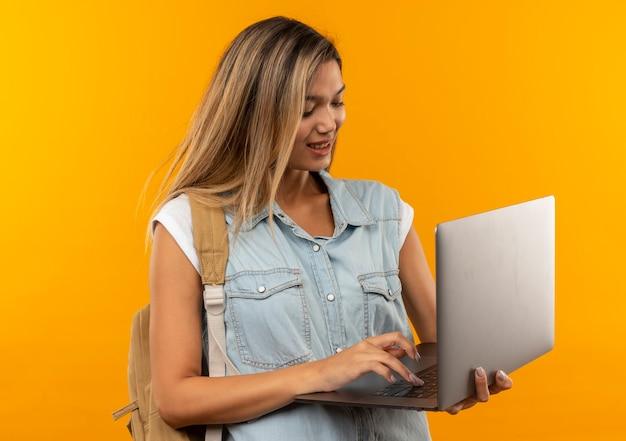 Erfreutes junges hübsches studentenmädchen, das rückentasche unter verwendung des auf orange wand lokalisierten laptops trägt