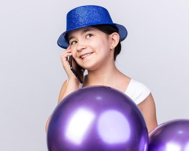 Erfreutes junges kaukasisches mädchen, das blauen partyhut trägt, der mit heliumballons steht, die am telefon lokalisiert auf weißer wand mit kopienraum sprechen