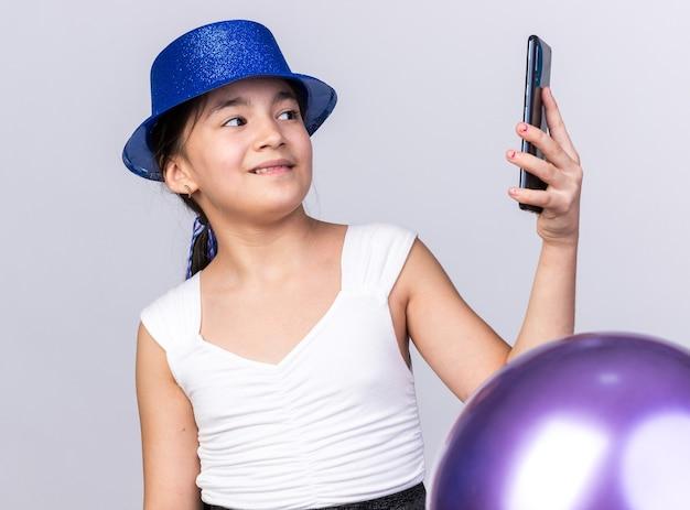 Erfreutes junges kaukasisches mädchen, das blauen partyhut trägt, der mit heliumballons steht, die telefon lokalisiert auf weißer wand mit kopienraum betrachten
