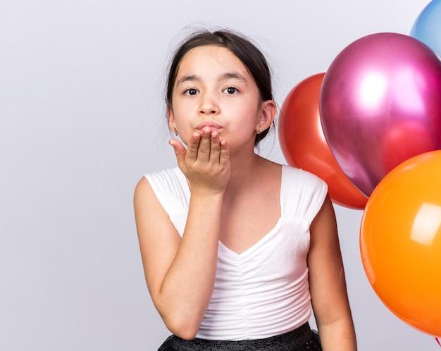 Erfreutes junges kaukasisches mädchen, das mit heliumballons steht und einen kuss mit der hand sendet, isoliert auf weißer wand mit kopierraum