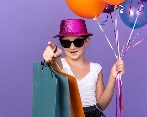 Erfreutes junges kaukasisches mädchen in der sonnenbrille mit violettem partyhut, der heliumballons und einkaufstaschen hält, die nach vorne lokalisiert auf lila wand mit kopienraum zeigen