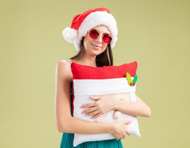 Erfreutes junges kaukasisches mädchen in sonnenbrille mit weihnachtsmütze umarmt weihnachtsmannkissen