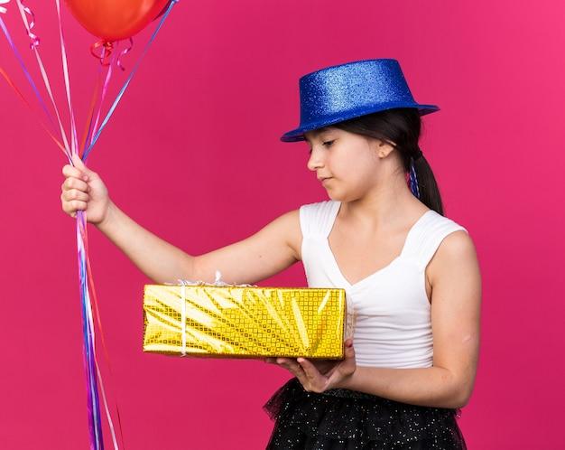 Erfreutes junges kaukasisches mädchen mit blauem partyhut, das geschenkbox betrachtet und heliumballons isoliert auf rosa wand mit kopienraum hält