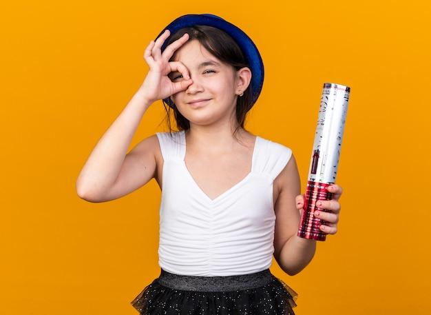Erfreutes junges kaukasisches mädchen mit blauem partyhut, der konfettikanone hält und durch finger isoliert auf oranger wand mit kopierraum