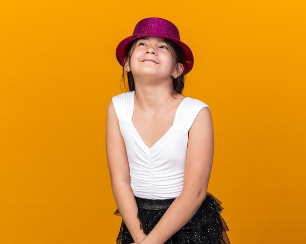 Erfreutes junges kaukasisches mädchen mit lila parteihut, der lokalisiert auf orange wand mit kopienraum sucht