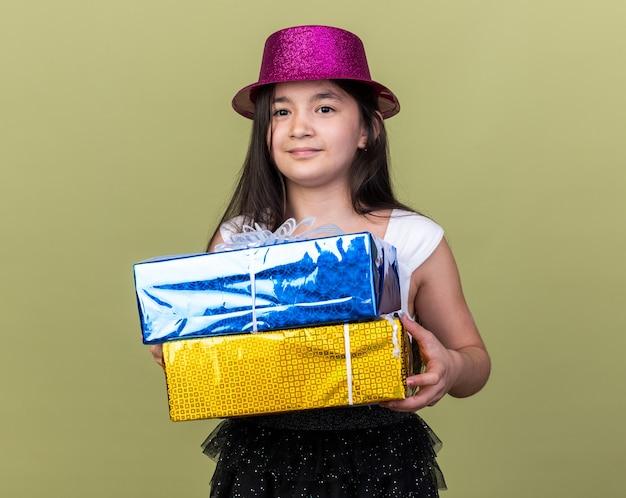 Erfreutes junges kaukasisches mädchen mit lila partyhut, das geschenkboxen isoliert auf olivgrüner wand mit kopienraum hält