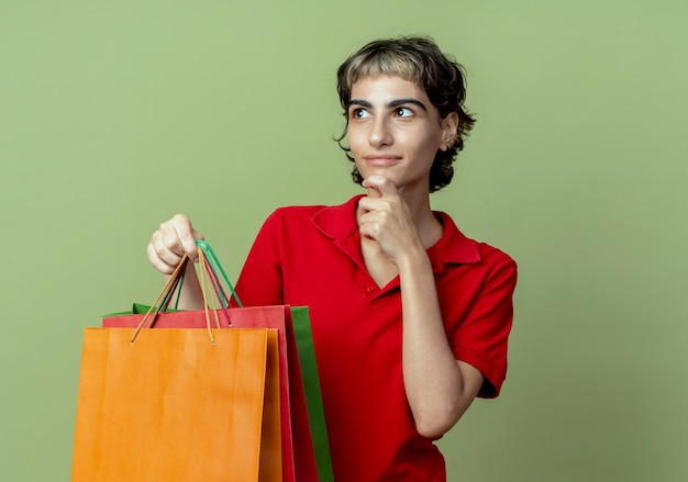 Erfreutes junges kaukasisches mädchen mit pixie-haarschnitt, der einkaufstaschen hält, die kinn berühren, das seite lokalisiert auf olivgrünem hintergrund mit kopienraum betrachtet
