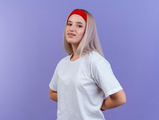 Erfreutes junges kaukasisches sportliches mädchen mit zahnspangen, die stirnband tragen
