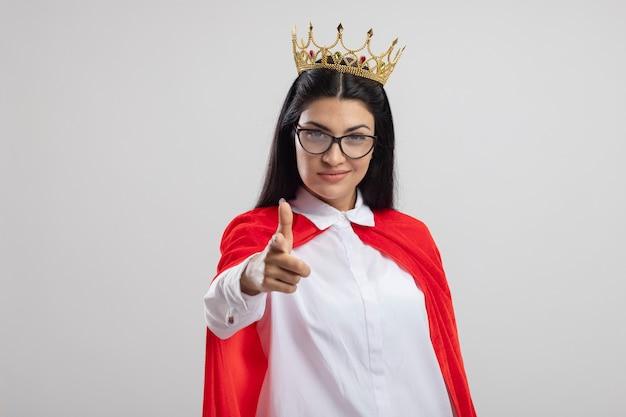 Erfreutes junges kaukasisches superheldenmädchen, das brille und krone trägt kamera betrachtet pistolengeste lokalisiert auf weißem hintergrund mit kopienraum