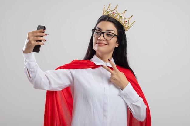 Erfreutes junges kaukasisches superheldenmädchen, das brille und krone tut friedenszeichen nimmt, das selfie lokalisiert auf weißem hintergrund mit kopienraum nimmt