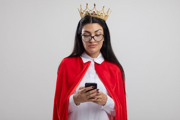 Erfreutes junges kaukasisches superheldenmädchen, das brille und krone unter verwendung des mobiltelefons lokalisiert auf weißem hintergrund mit kopienraum trägt
