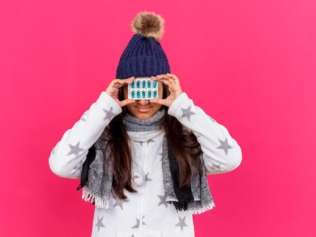 Erfreutes junges krankes mädchen, das wintermütze mit schal bedeckt augen mit pillen auf rosa isoliert trägt