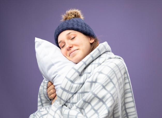 Erfreutes junges krankes mädchen mit geschlossenen augen, das weißes gewand und wintermütze mit schal trägt, der in kariertes umarmtes kissen gewickelt wird