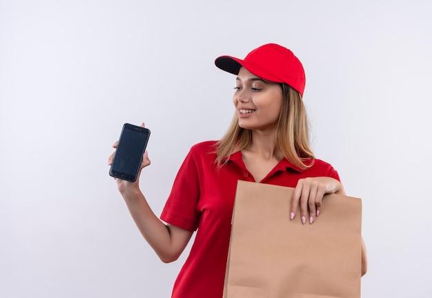 Erfreutes junges liefermädchen, das rote uniform und kappe hält, die papiertüte hält und telefon in ihrer hand lokalisiert auf weißem hintergrund betrachtet