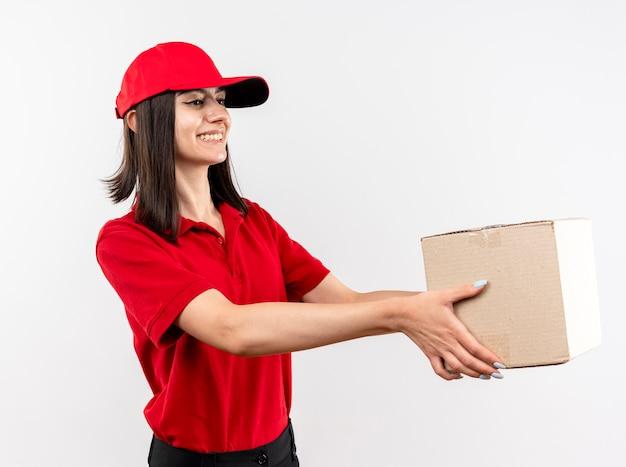 Erfreutes junges liefermädchen, das rote uniform und kappe trägt, die boxpaket zu einem kunden gibt, der fröhlich über weißer wand stehend lächelt