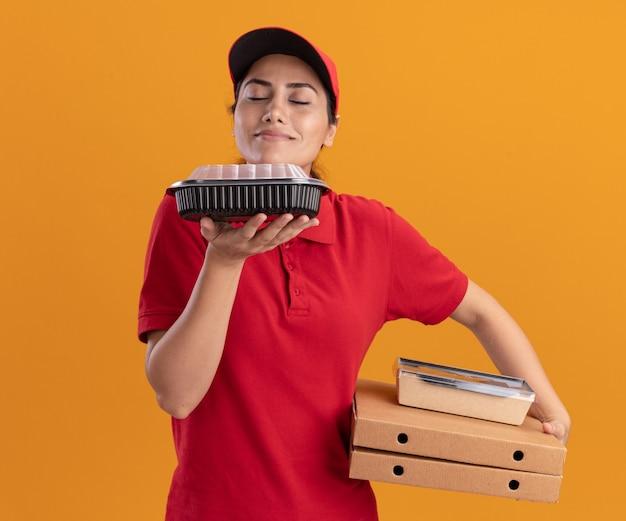 Erfreutes junges liefermädchen, das uniform und kappe trägt, die pizzaschachteln hält und lebensmittelbehälter in ihrer hand schnüffelt lokalisiert auf orange wand