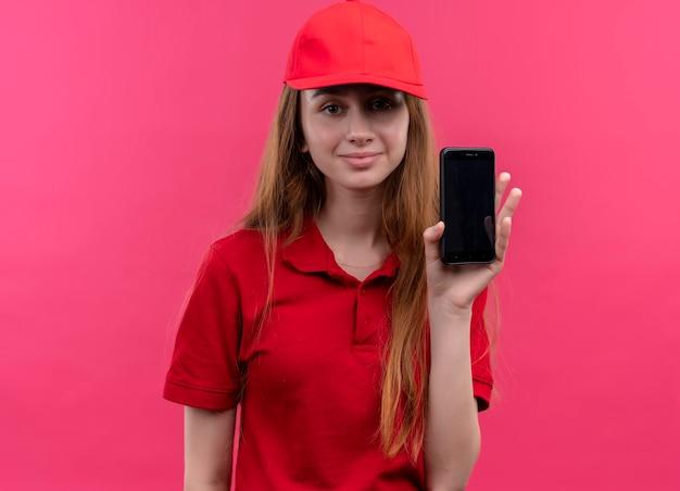 Erfreutes junges liefermädchen in der roten uniform, die handy auf lokalisiertem rosa raum hält