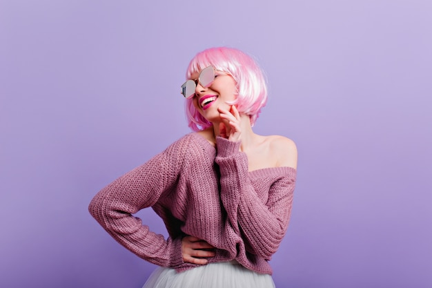 Erfreutes junges mädchen in perücke und sonnenbrille, die spaß haben foto des wunderbaren weiblichen modells mit rosa haaren, die lächeln, während sie auf lila wand tanzen.