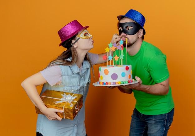Erfreutes junges mädchen mit rosa hut und maskerade-augenmaske hält geschenkbox und hält wange eines fröhlichen, gutaussehenden mannes mit blauem hut, der maskerade-augenmaske trägt und geburtstagskuchen hält
