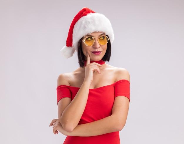 Erfreutes junges mädchen mit weihnachtsmütze und brille, das auf das seitlich berührende gesicht schaut, das auf weißem hintergrund mit kopienraum isoliert ist?