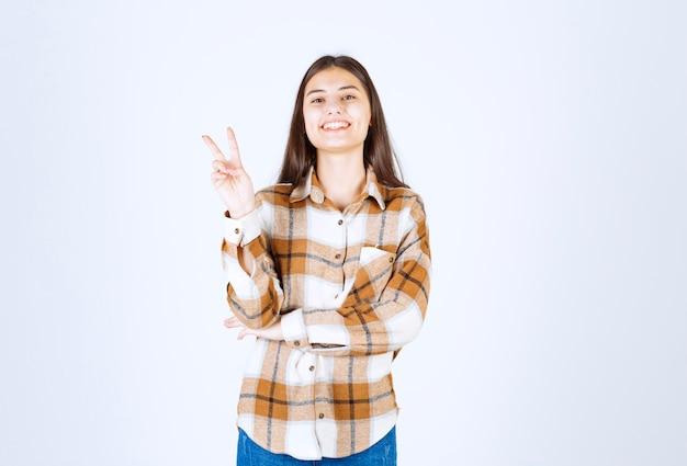 Erfreutes junges mädchenmodell, das victory-zeichen zeigt.