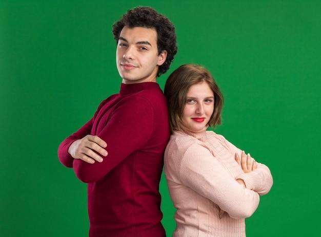 Erfreutes junges paar am valentinstag, das in der profilansicht mit geschlossener haltung steht, die sich rücken an rücken lehnt und nach vorne isoliert auf grüner wand blickt