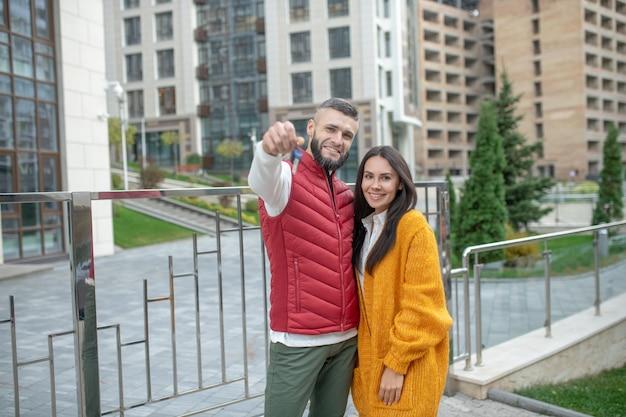 Erfreutes junges paar, das ihnen die schlüssel zeigt, während sie in die neue wohnung ziehen