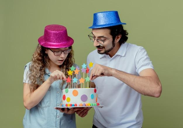 Erfreutes junges paar, das rosa und blauen hut trägt, der geburtstagstorte hält und betrachtet